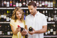 Casual couple looking at wine bottle Royalty Free Stock Photos