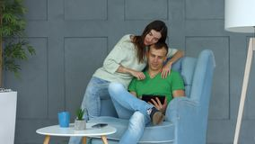 Casual couple sharing tablet pc siting on armchair stock footage