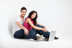 Casual couple sitting down with laptop Royalty Free Stock Photo