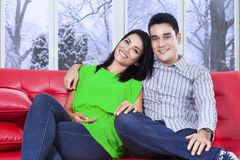 Casual couple sitting on red sofa Stock Image