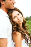 Casual couple smiling. Young woman smiling at camera as she leans on her man Stock Photography