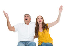 Casual couple smiling with arms raised Stock Image