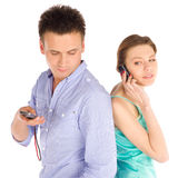 Casual Couple Talking on the Phone. Young casual couple standing back to back, woman talking on the phone, man checking sms, isolated on white background Stock Photography