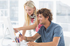Casual couple using computer in bright office Stock Photos