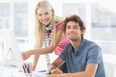 Casual couple using computer in bright office Stock Photography
