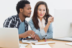 Casual couple using computer in office Royalty Free Stock Images