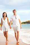 Casual couple walking on beach holding hands. On honeymoon travel vacation holidays. Young multi-ethnic couple lovers, Asian women and Caucasian man Royalty Free Stock Photography