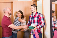 Casual couple welcomes friends Royalty Free Stock Photos