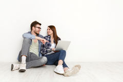 Casual couple working with laptop, studio shot Stock Images