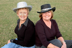 Casual cowgirls. Smiling mature woman wearing cowboy hats and sitting in the grass Stock Photo