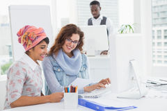 Casual coworkers smiling and suing computer Stock Photo