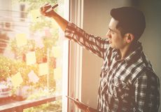 Casual creative business man writing ideal and goal on to the windows. Casual creative business man is writing ideal and goal on to the windows Royalty Free Stock Images