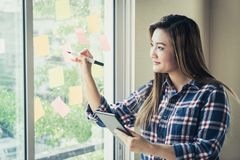 Casual creative business man writing ideal and goal on to the windows. Casual creative business man is writing ideal and goal on to the windows Royalty Free Stock Photography