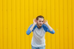 Curious man overhearing and listening something on a yellow background. Eavesdropping concept. Copy space. Stock Photo