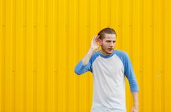 Curious man overhearing and listening something on a yellow background. Eavesdropping concept. Copy space. Stock Photography