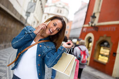 Casual day out shopping. Young woman out shopping chatting on the phone Royalty Free Stock Images