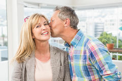 Casual designer giving his colleague kiss on cheek Stock Photography