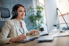 Casual designer woman working in a design studio and listen music. Casual happy designer woman working in a design studio and listen music stock photos