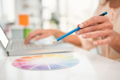 Casual designer working with laptop and colour chart Royalty Free Stock Images