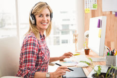 Casual designer working and smiling at camera Royalty Free Stock Photography