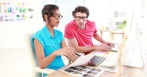 Casual designers working on a photo catalog. Smiling casual designers working on a photo catalog at office stock footage