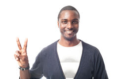 Casual dressed afro-american man with blue sweater and showing victory sign. Royalty Free Stock Image