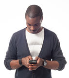 Casual dressed black man looking his mobile phone. Isolated on white Royalty Free Stock Photography