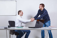 Casual dressed businessmen shaking hands. Casual dressed businessmen at the office shaking hands Royalty Free Stock Photography