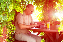 Casual dressed man with gadget and glass of orange. Aged man pointing into screen of black tablet PC sitting inside wooden pavilion in green park with curled Royalty Free Stock Images