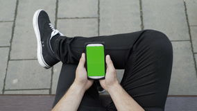Casual dressed man sitting on bench in a park looking and using his smartphone with chroma display with green screen. Casual dressed man sitting on bench in a stock video footage