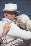 Casual elderly couple embracing and able to kiss at daytime Royalty Free Stock Photos