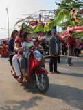 Casual family pass by the procession of Sihanoukville annual Carnival Stock Photography