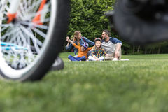 Casual family spending time in park at daytime, bicycle on foreground Stock Images