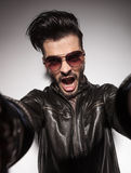 Casual fashion man shouting while holding the camera Stock Photos