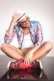 Casual fashion man sitting with his legs crossed. While looking away from the camera. He is holding his right hand on his hat Royalty Free Stock Photo