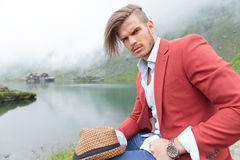 Casual fashion man is sitting near a lake Stock Images