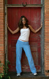 Casual Fashion Model 1. Beautiful fashion model in casual outfit with white top and blue pants posing in front of rustic weathered red door stock photo