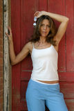 Casual Fashion Model 4. Beautiful fashion model in casual outfit with white top and blue pants posing in front of rustic weathered red door royalty free stock image