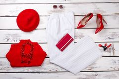 Casual fashionable woman`s appeal on white wood background. Red and white clothing and accessories Stock Photos