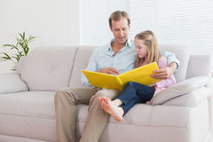 Casual father and daughter looking at photo album royalty free stock image