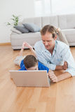 Casual father and son using laptop on the floor Stock Photo