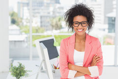 Casual female artist with arms crossed at bright office Stock Photography