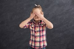 Casual female child covering eyes with hands royalty free stock photography
