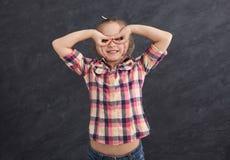 Casual female child holding fingers near eyes like glasses stock photography