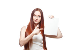 Casual female holding and pointing on sign. Horizontal studio portrait of young attractive green-eyed caucasian female with long natural straight red hair which royalty free stock images