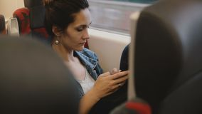 Casual female passenger on the train sits in a comfortable seat using smartphone e-commerce app, looking at the window. Relaxed traveler woman spending travel stock video