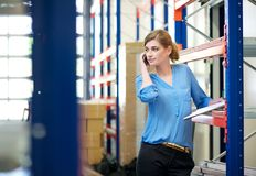 Casual female warehouse employee talking on mobile phone Stock Photo