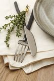 Casual fine dining table setting with natural, organic style fork, knife, napkin and plate, accented with a sprig of fresh thyme Stock Images