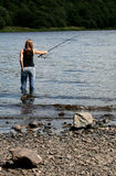 Casual Fishing. Fisherwoman in nice casual relaxed pose with one hand in back pocket, and and up to her knees in water for the catch of the day royalty free stock images