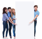 Casual friends pointing and showing you a blank banner Royalty Free Stock Photo